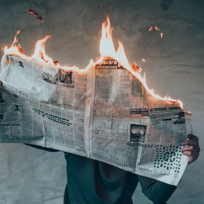 photograph of a person holding a burning news paper