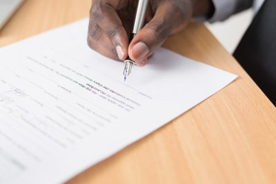 photograph of a hand with a pen signing a document